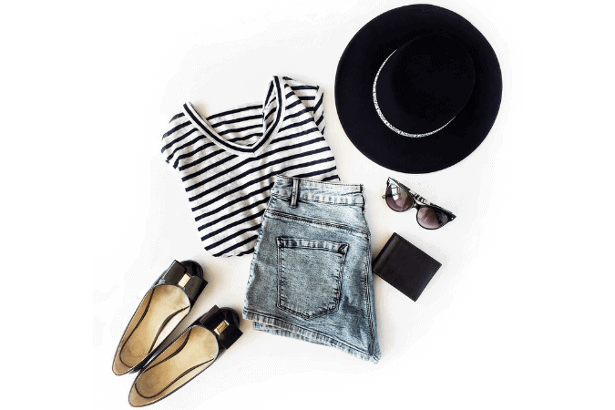 An overlay of a woman's outfit with a black hat, shoes a stripped black and white tee shirt and jeans with accessories