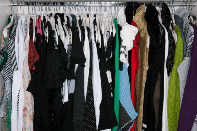 A messy and cluttered open closet