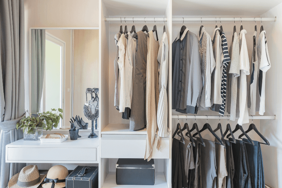 A white closet filled with an elegant wardrobe of matching clothes and very organized
