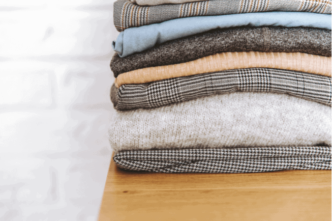 A pile of neatly folded thin sweaters that are neutral colors on a wood desk
