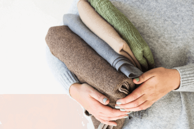 Woman holding a neatly folded sweaters